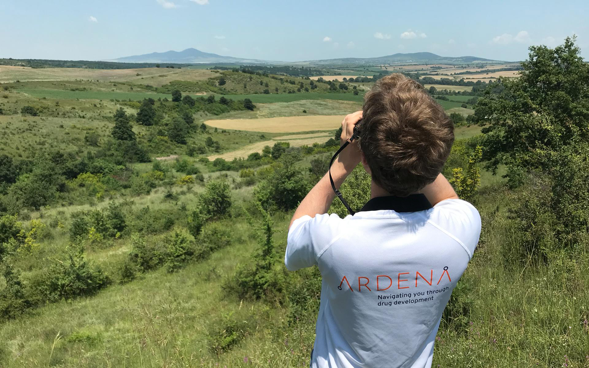 Man wearing a Ardena shirt looking out into the mountains